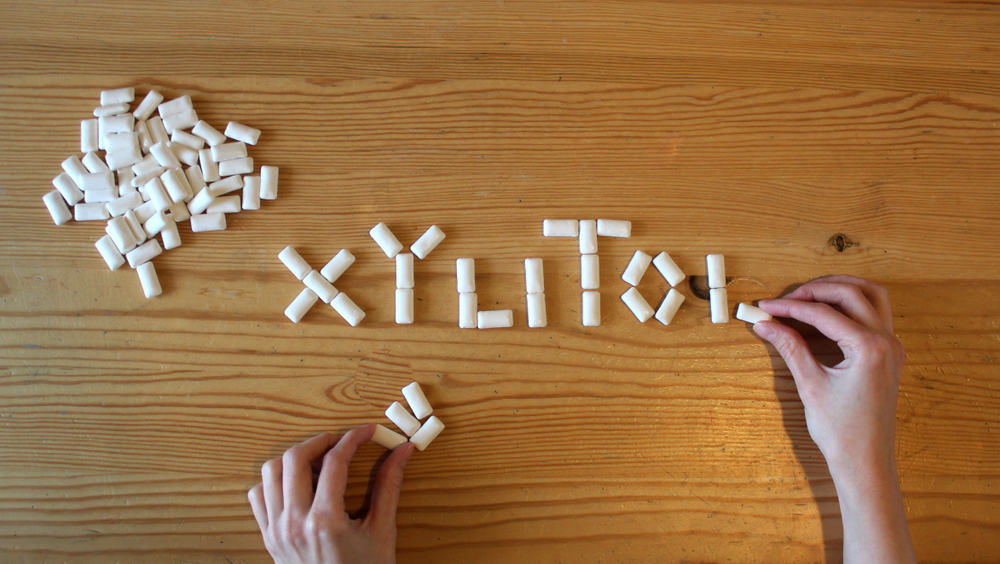 Woman spelling out the word Xylitol in chewing gum pieces
