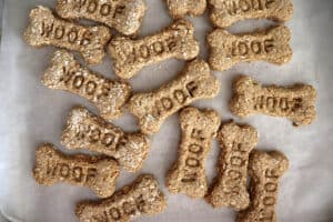 "Overhead shot of bone shaped dog treats with the word ""woof"" stamped in them"