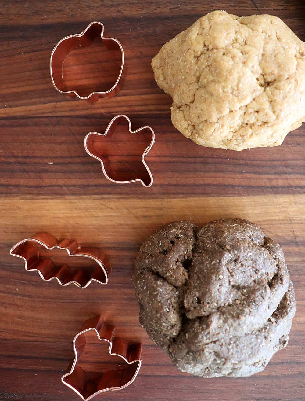 Two doughs with cookie cutters on a wooden cutting board
